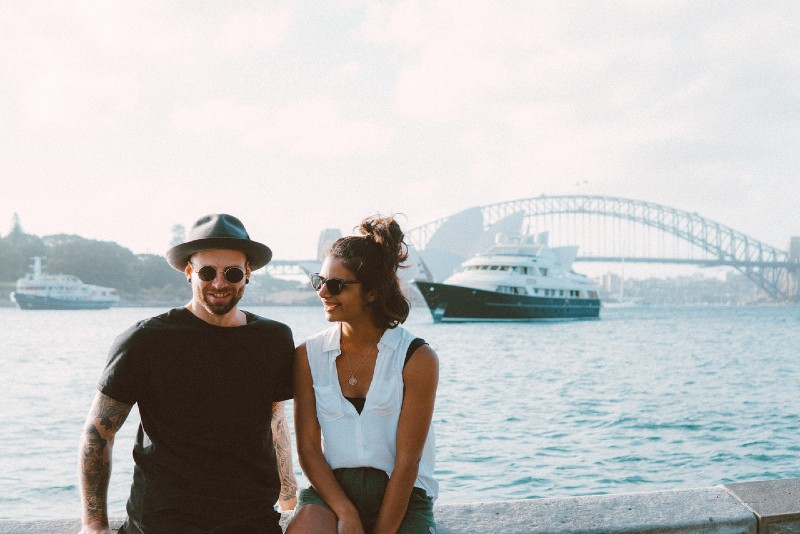 smiling woman looking at man while sitting near water