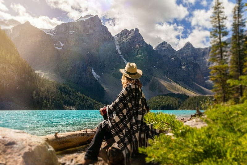 woman looking at mountain while sitting on rock