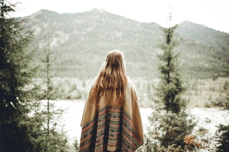 woman in brown poncho looking at mountain