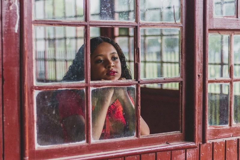 woman in red top looking through window