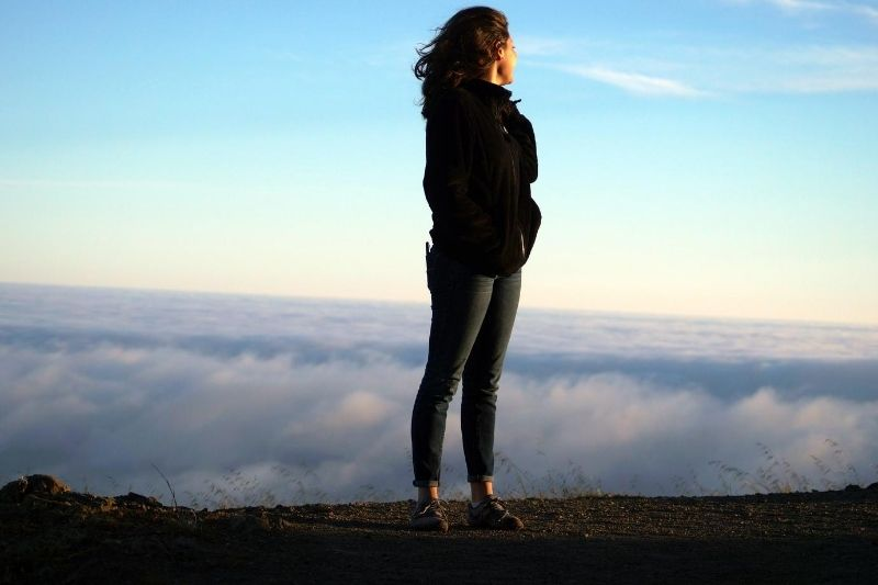 woman looking behind the cloudy space behind the mountain she is standing
