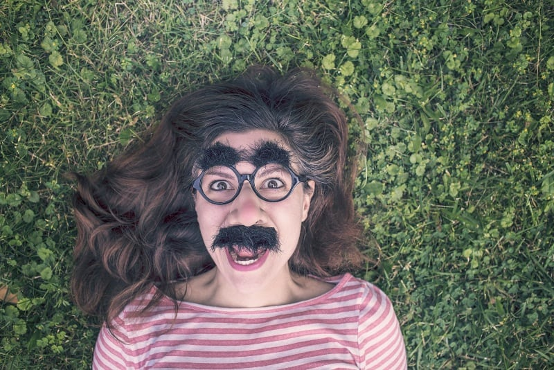 woman with funny mask lying on grass