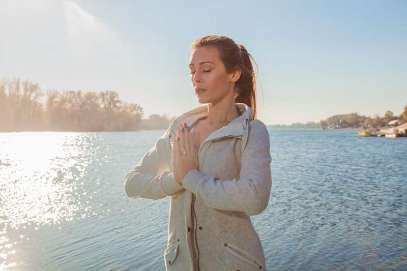 woman meditating outdoors standing near the body of water