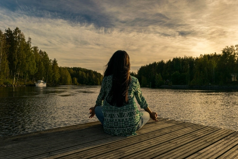 woman meditating while sitting on dock