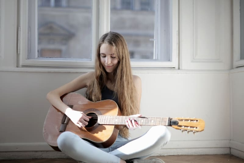 woman playing guitar while sitting on floor near window