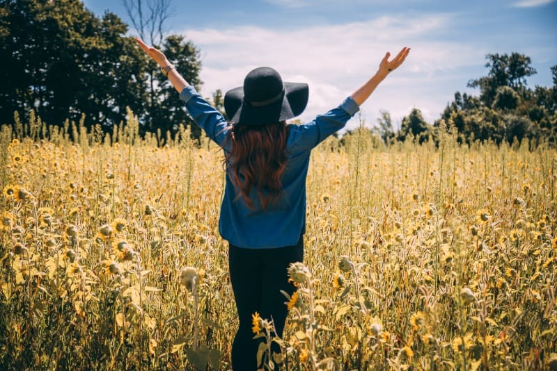 woman raising both hands while standing in sunflowers field