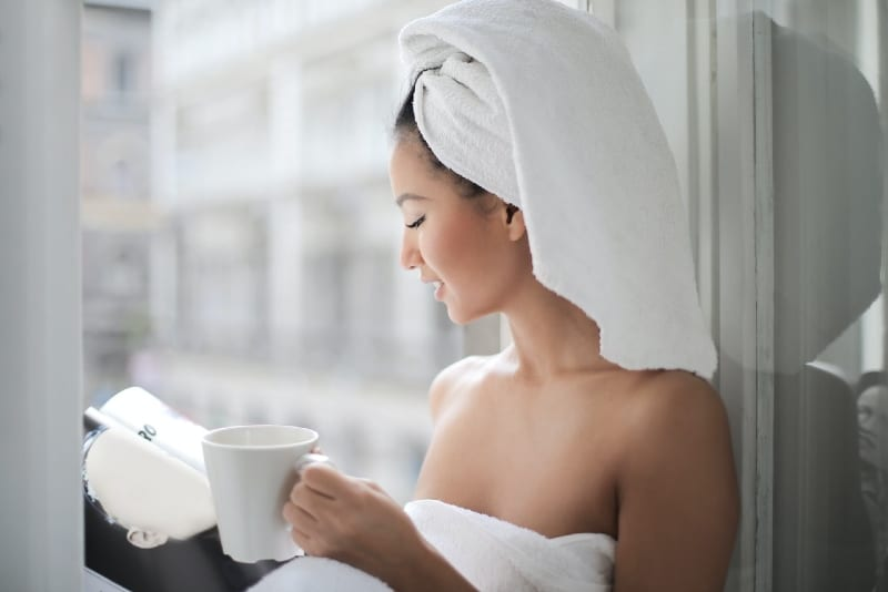 woman with towel on her head reading magazine near window