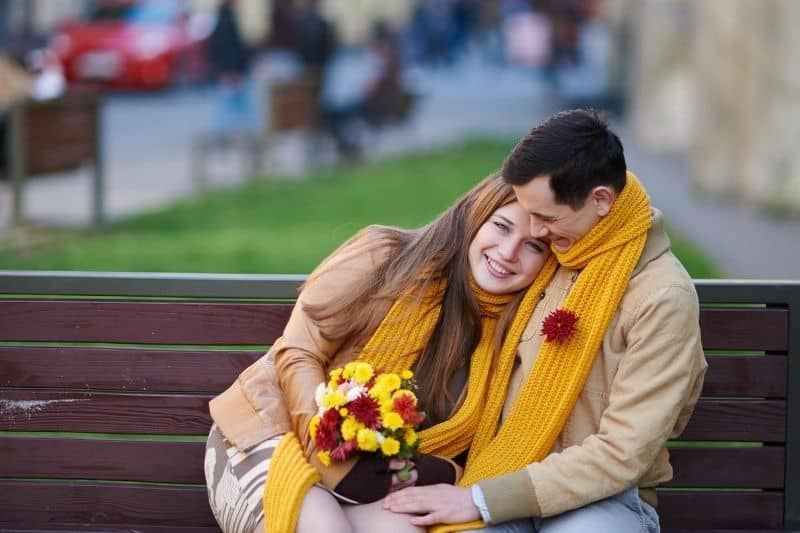 woman receiving a bouquet of flower from her man sitting and hugging her on the bench outdoors