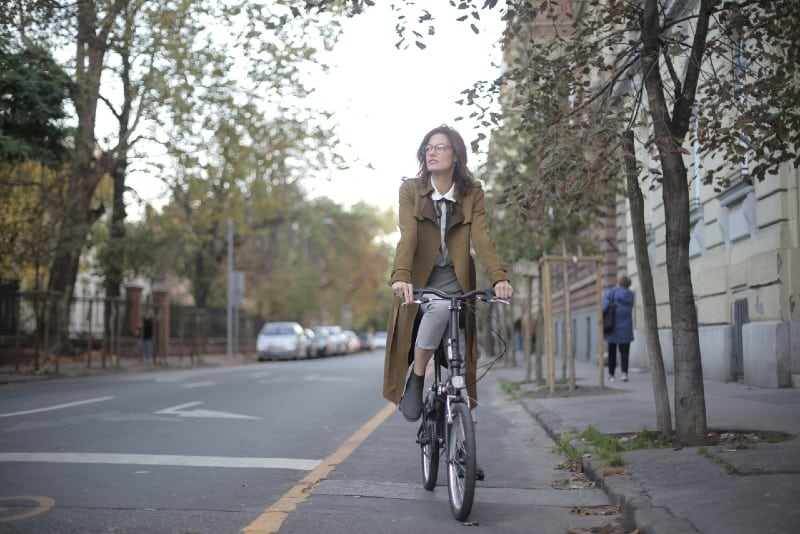 woman in brown coat riding a bicycle