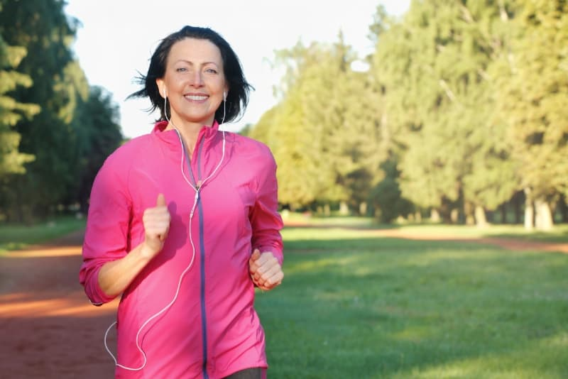 woman with headphones running in park