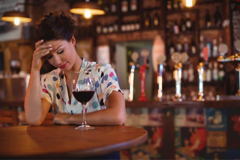woman sitting in the bar upset having a drink holding her forehead