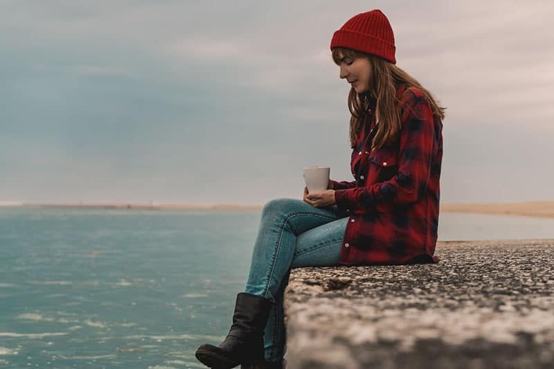 woman sitting near the sea holding a mug wearing red bonnet and checkered top