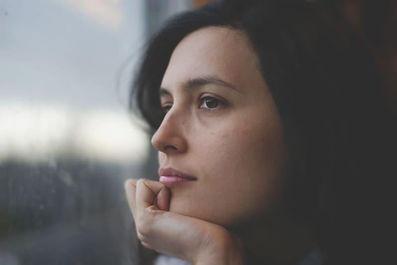 woman with black hair sitting near window