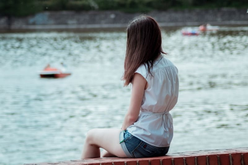 woman in white top sitting on concrete bench
