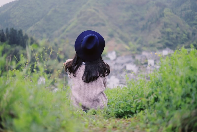 woman with blue hat sitting on grass