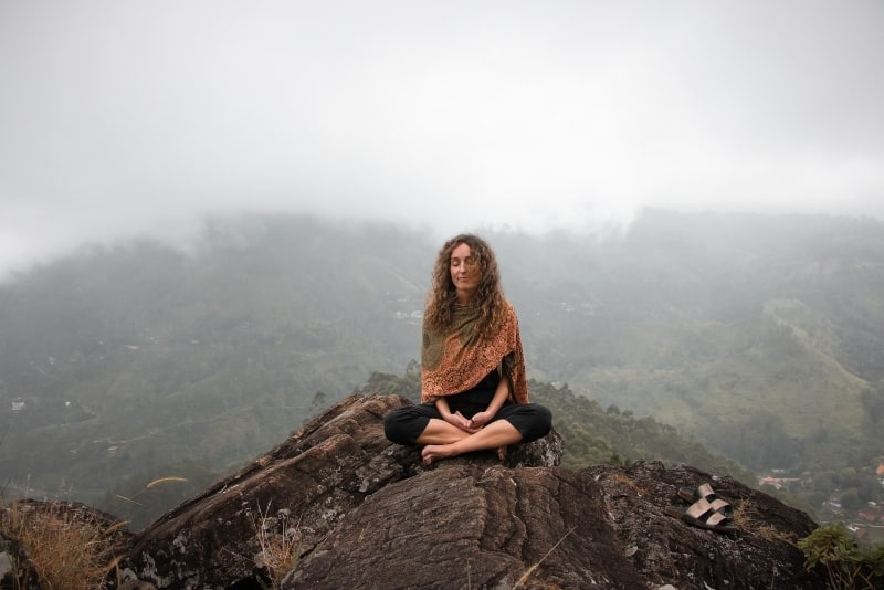 woman with eyes closed sitting on rock