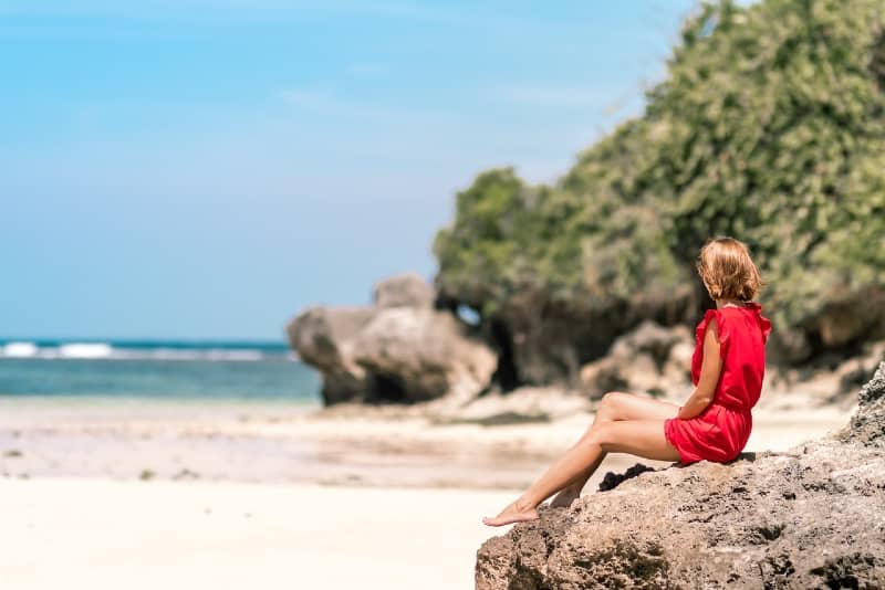woman in red dress sitting on rock