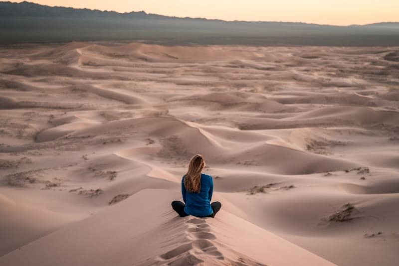 woman in blue top sitting on sand