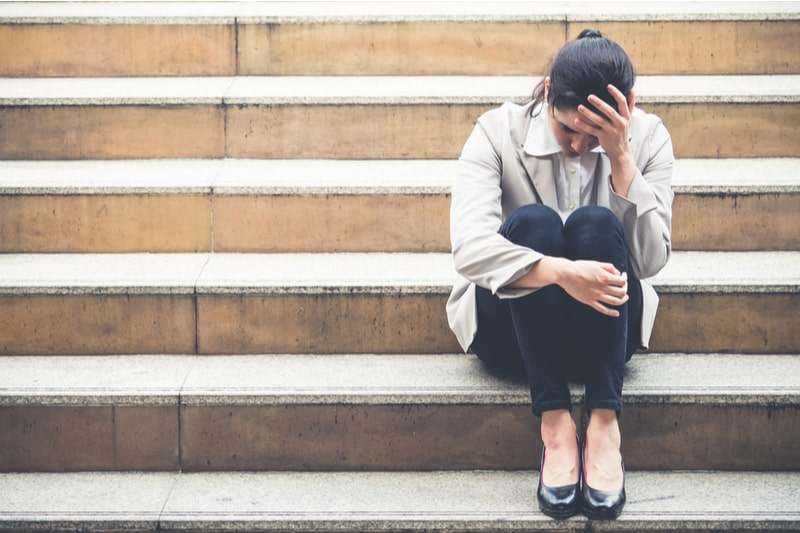 woman sitting on stairs of the building wearing office suit sadly holding her head