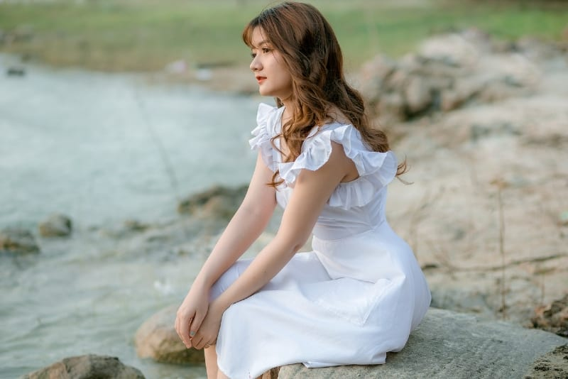 woman in white dress sitting on stone