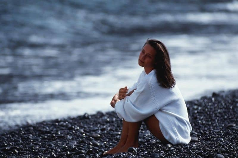 woman sitting pensively on the small rocks on the seashore wearing white big top