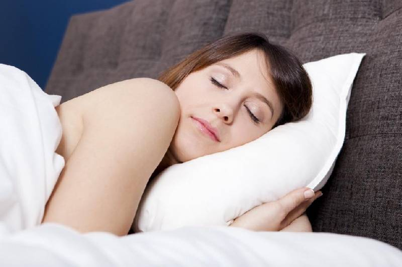 woman sleeping soundly with while pillows and gray brown head board