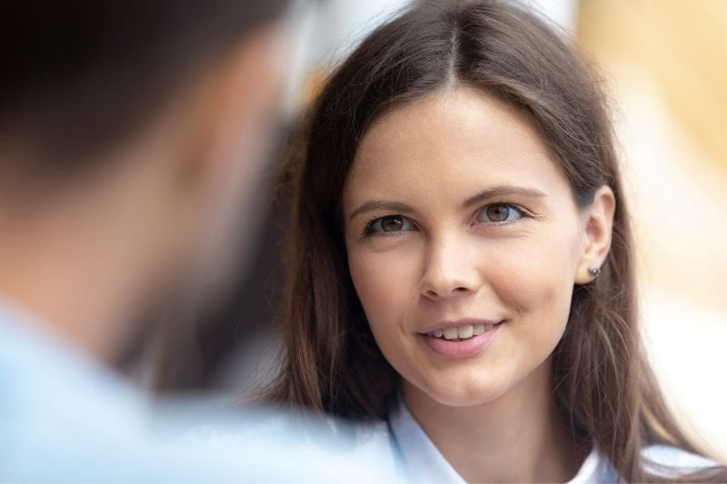 woman smiling talking to a guy showing his back view only