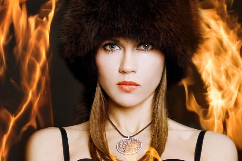 woman standing around with fire wearing a thick fur headcap