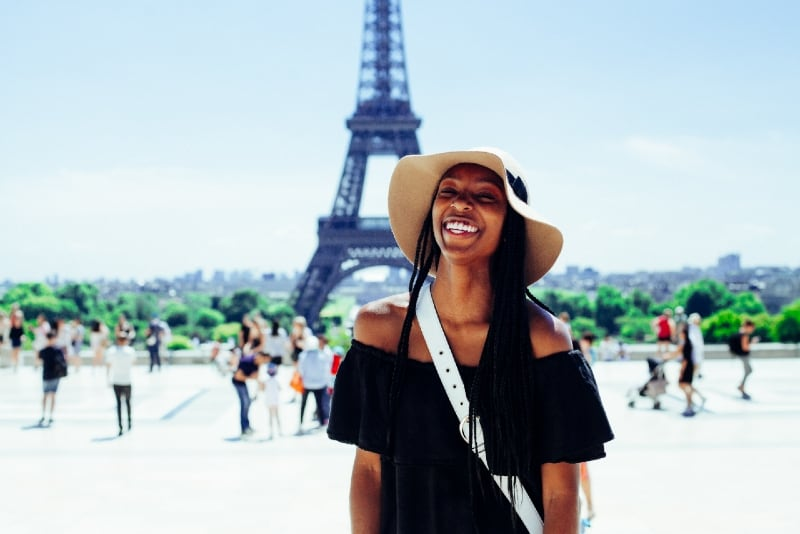 smiling woman with hat standing behind eiffel tower