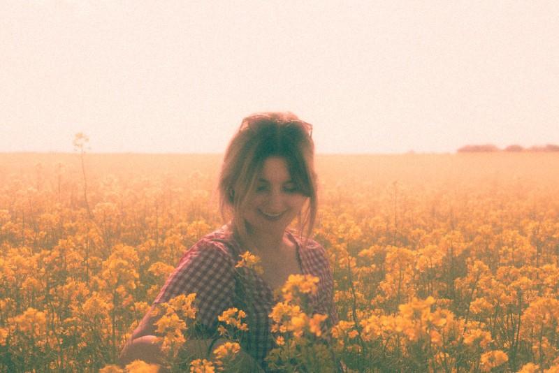 woman standing in yellow flower field