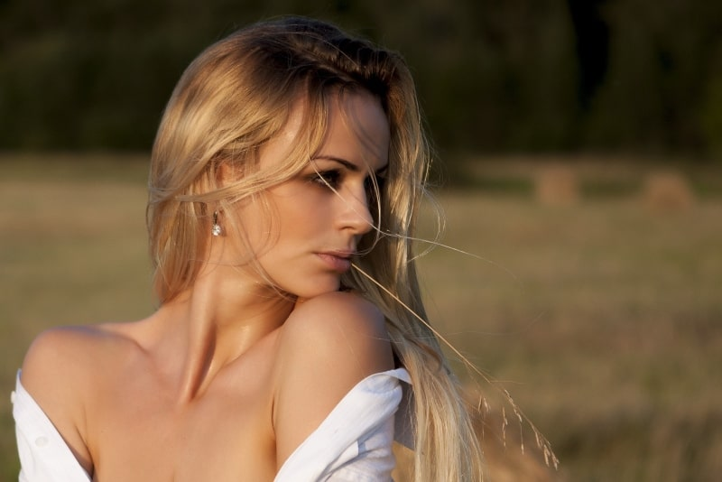 blonde woman in white shirt standing in the field