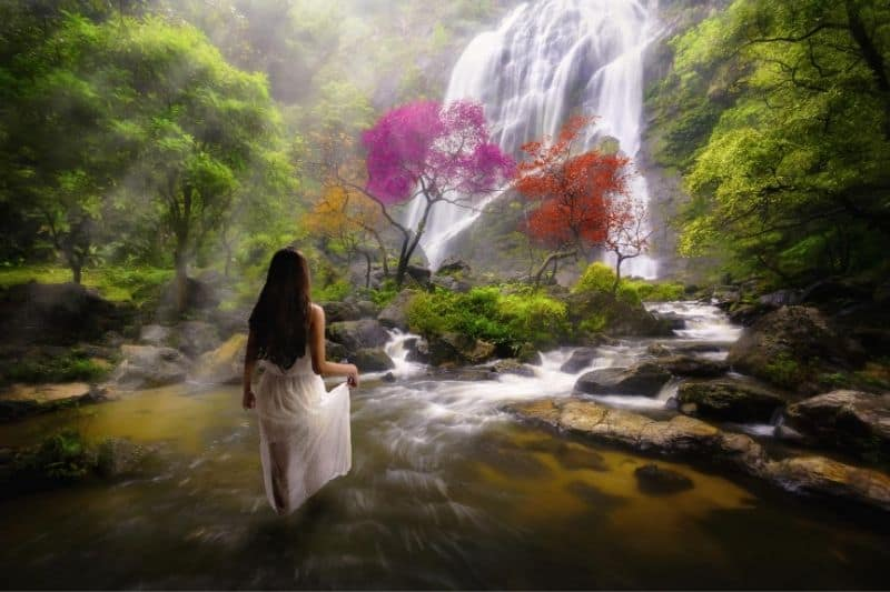 woman standing in the water near the waterfalls in the dreamy forest