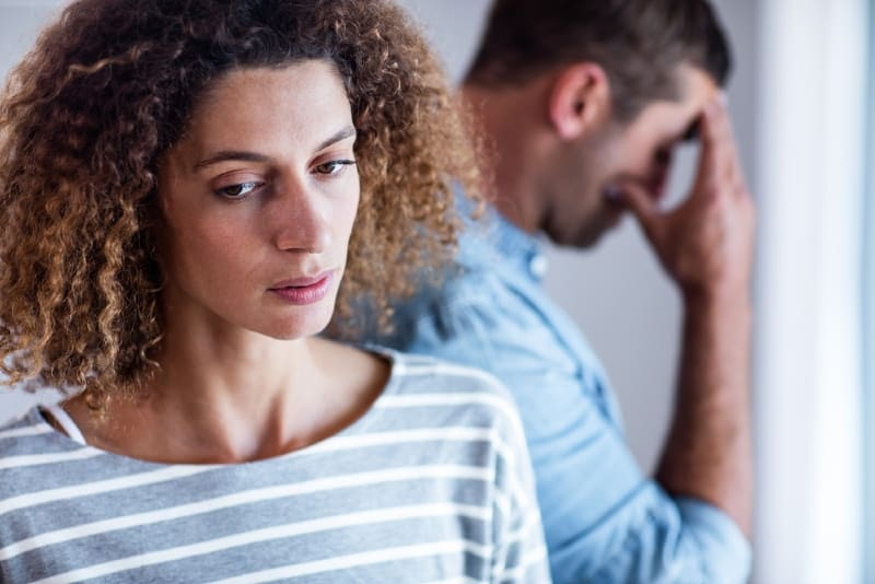 woman in striped top standing near sad man
