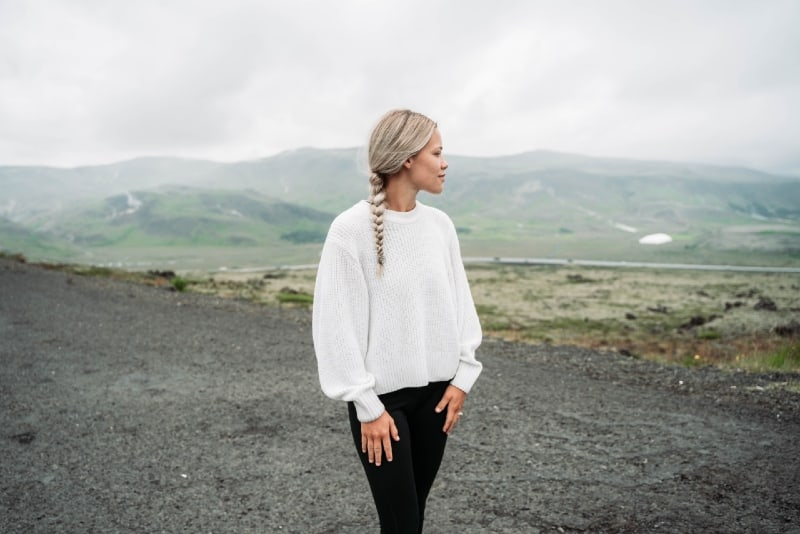 blonde woman in white top standing near mountain