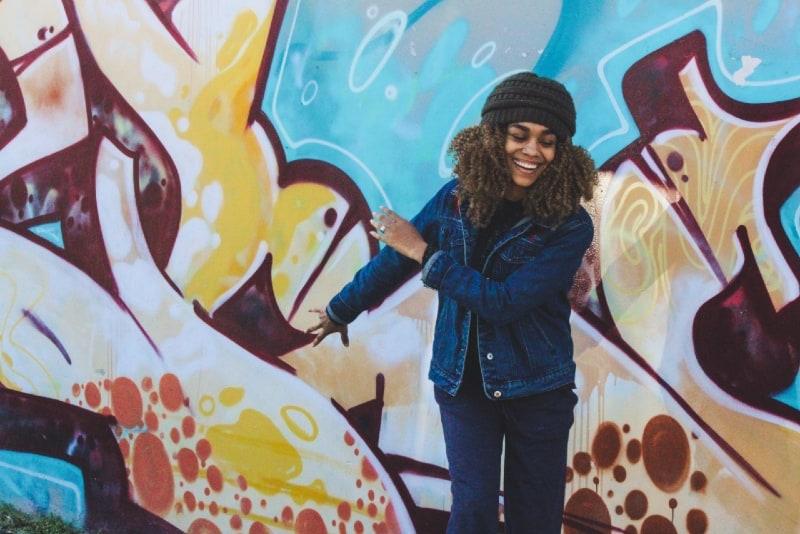 happy woman standing near graffiti wall