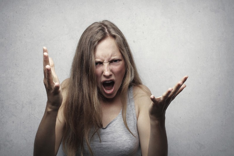 angry woman in gray top standing near white wall