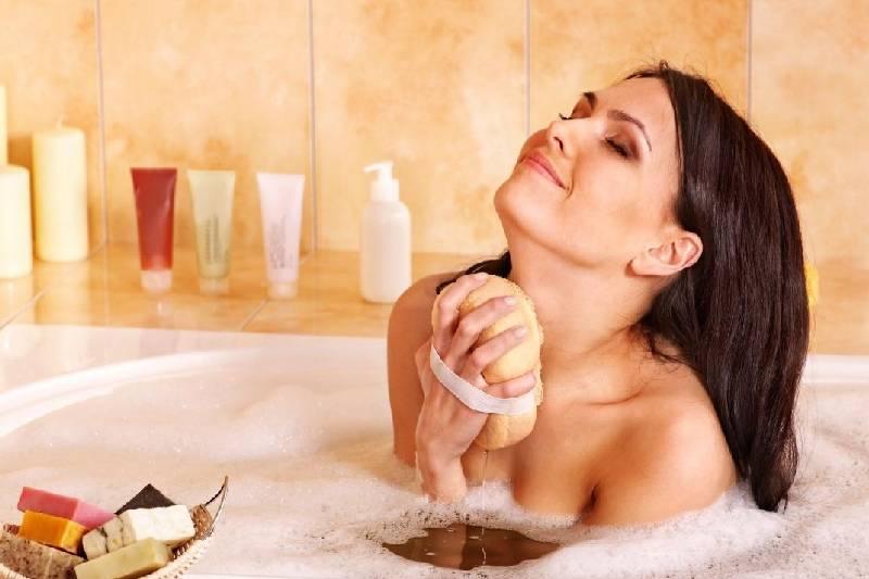 woman taking a bubble bath in a bath tub rubbing with sponge happily
