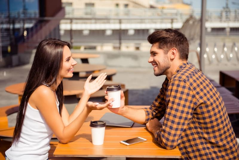 smiling woman talking to man while sitting at table