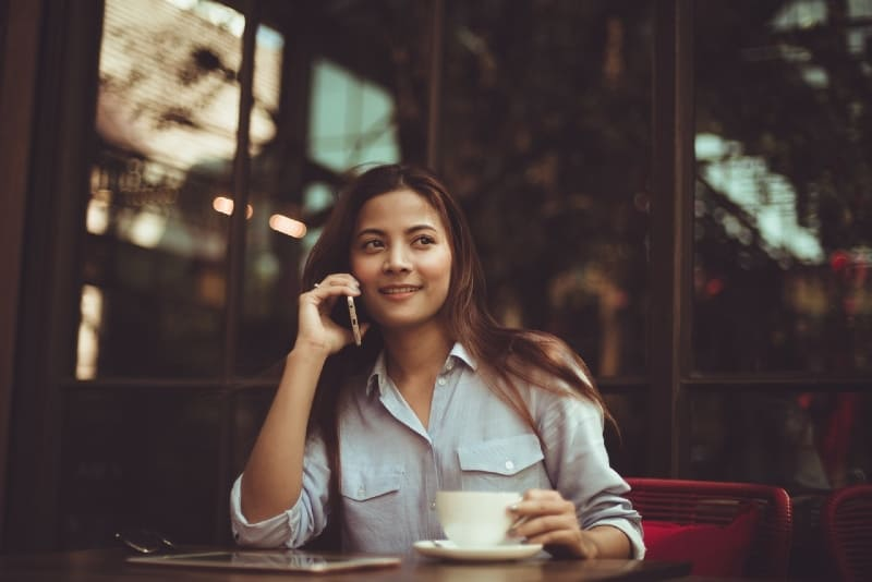 woman talking on phone while sitting at table