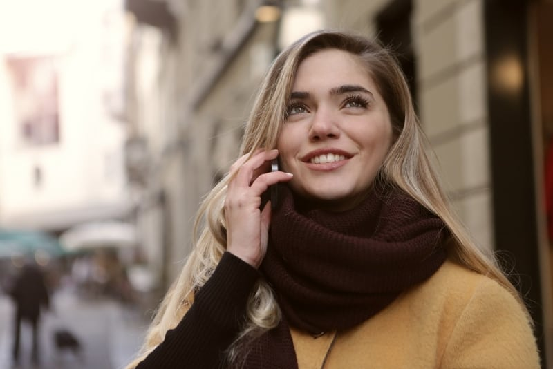 blonde woman with brown scarf talking on the phone