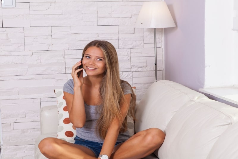 blonde woman talking on phone while sitting on sofa