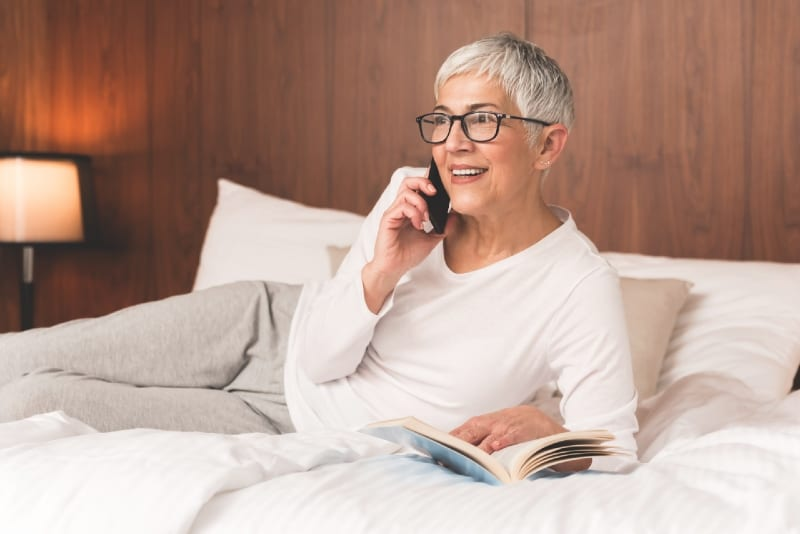 woman talking on the phone while sitting on bed