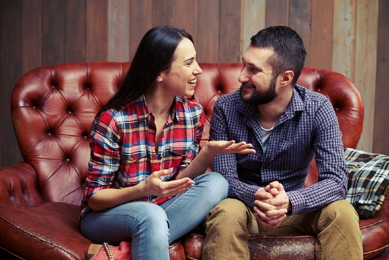 smiling woman talking to man while sitting on couch