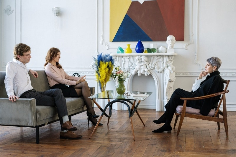 woman talking to therapist while sitting on sofa near man