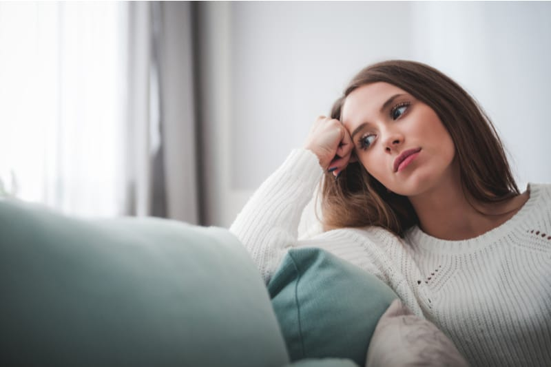 woman thinking deeply sitting by the couch near the windows