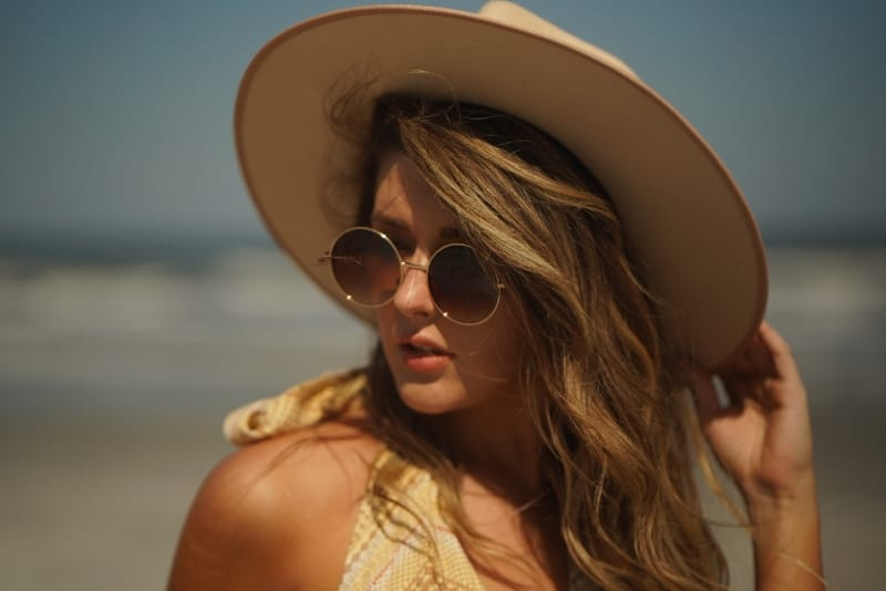 woman with sunglasses touching her hat on beach