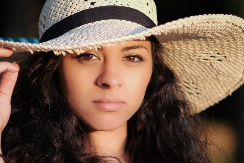 woman with brown eyes touching her hat