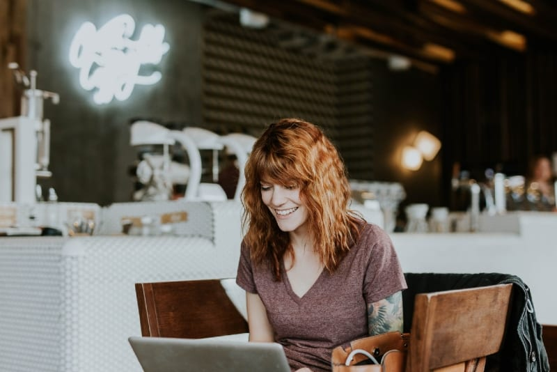 smiling woman using laptop while sitting on chair
