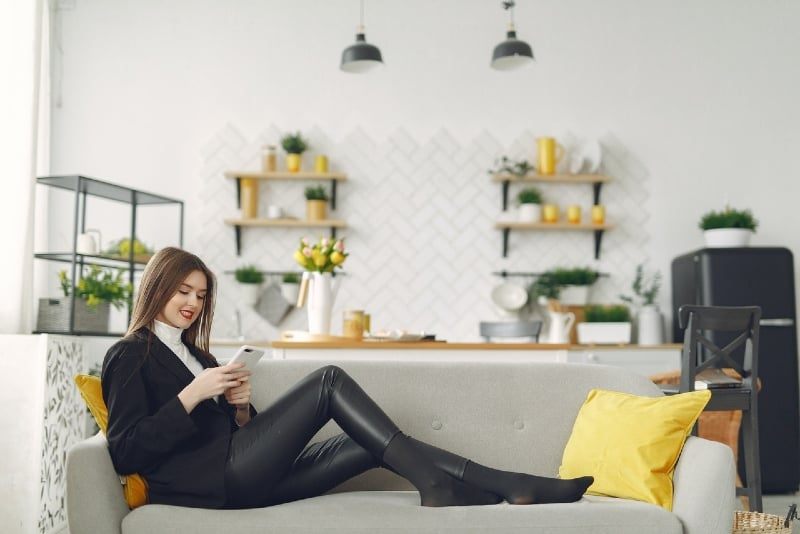 woman using phone while sitting in living room