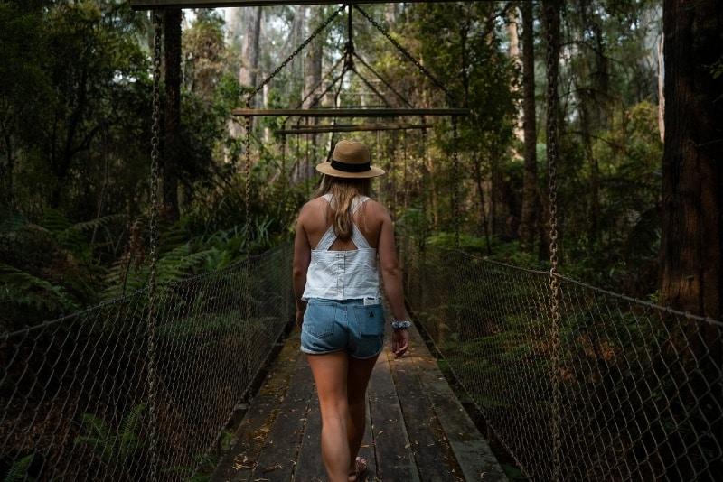 woman with hat walking on bridge